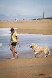 Ένα αγόρι με ένα σκυλί στην παραλία Στοκ εικόνα με δικαίωμα ελεύθερης χρήσης