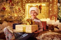 Ένα αγόρι με ένα δώρο από την εστία στο δωμάτιο Χριστουγέννων Στοκ φωτογραφία με δικαίωμα ελεύθερης χρήσης