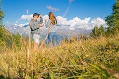 Ένα αγόρι με ένα κορίτσι στα βουνά στο υπόβαθρο των θερινών βουνών του δύσκολου τοπίου με τα δέντρα κάθισμα Στοκ Εικόνες
