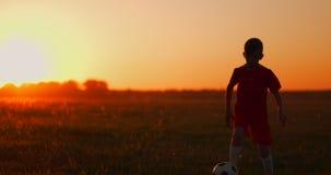 Ένα αγόρι με ένα ποδόσφαιρο τρέχει στη κάμερα στο ηλιοβασίλεμα απόθεμα βίντεο