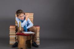 Ένα αγόρι με τη χρυσή συνεδρίαση μανδρών καλαμιών σε έναν θρόνο των βιβλίων Στοκ Εικόνα