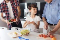 Ένα αγόρι με τον πατέρα και τον παππού του που προετοιμάζουν μια σαλάτα για την ημέρα των ευχαριστιών Στοκ Εικόνες