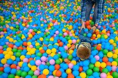 Ένα αγόρι με τον πατέρα στο δωμάτιο παιχνιδιού με πολλές μικρές χρωματισμένες σφαίρες στοκ φωτογραφία με δικαίωμα ελεύθερης χρήσης