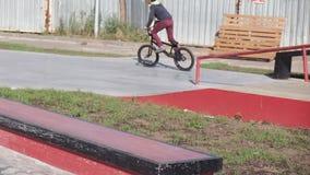 Ένα αγόρι οδηγά τα τεχνάσματα ανακύκλωσης BMX σε ένα skateboard πάρκο σε μια ηλιόλουστη ημέρα Έξοχος σε αργή κίνηση απόθεμα βίντεο