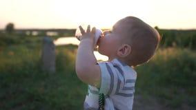 Ένα αγόρι πίνει ένα ποτό από ένα μπουκάλι μωρών που είναι στη φύση στο ηλιοβασίλεμα, σε αργή κίνηση φιλμ μικρού μήκους