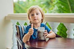 Ένα αγόρι πίνει ένα ποτό από ένα χαρούπι Στοκ Φωτογραφίες