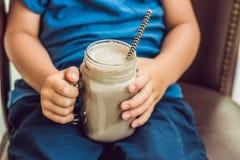 Ένα αγόρι πίνει ένα ποτό από ένα χαρούπι Στοκ φωτογραφία με δικαίωμα ελεύθερης χρήσης