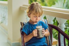 Ένα αγόρι πίνει ένα ποτό από ένα χαρούπι Στοκ Εικόνα