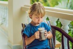 Ένα αγόρι πίνει ένα ποτό από ένα χαρούπι Στοκ Φωτογραφία
