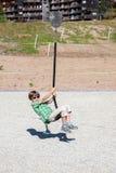 Ένα αγόρι παίζει με την ταλάντευση σχοινιών στην παιδική χαρά Στοκ Εικόνες