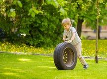 Ένα αγόρι παίζει με τη ρόδα του αυτοκινήτου στοκ εικόνες