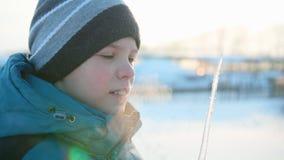 Ένα αγόρι που γλείφει ένα παγάκι Χιονώδης παγωμένη ηλιόλουστη ημέρα Διασκέδαση και παιχνίδια στο καθαρό αέρα Στοκ φωτογραφία με δικαίωμα ελεύθερης χρήσης