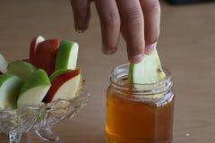 Ένα αγόρι που κτυπά ένα μήλο με το μέλι στοκ εικόνες
