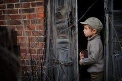 Ένα αγόρι που ντύνεται σε ένα αναδρομικό ύφος κρύβει το θησαυρό του σε ένα παλαιό σπίτι στοκ εικόνες με δικαίωμα ελεύθερης χρήσης