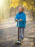 Ένα αγόρι που οδηγά ένα μηχανικό δίκυκλο στο πάρκο φθινοπώρου στοκ φωτογραφία