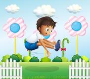 Ένα αγόρι που πηδά κοντά στο φράκτη Στοκ Εικόνες