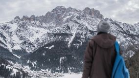 Ένα αγόρι που προσέχει τα βουνά που καλύπτονται με το χιόνι απόθεμα βίντεο