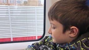 Ένα αγόρι που ταξιδεύει με το τραίνο, κοιτάζει μέσω του παραθύρου απόθεμα βίντεο