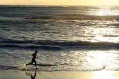 Ένα αγόρι που τρέχει στην παραλία κατά τη διάρκεια του ηλιοβασιλέματος στοκ εικόνες με δικαίωμα ελεύθερης χρήσης
