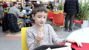 Ένα αγόρι που τρώει το γρήγορο φαγητό σε ένα εστιατόριο, δικαστήριο τροφίμων και που βυθίζει τις τηγανιτές πατάτες σε ένα πλαστικ απόθεμα βίντεο