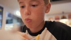 Ένα αγόρι σε έναν καφέ γρήγορου φαγητού Κατανάλωση των burgers και των τηγανιτών πατατών στους καφέδες γρήγορου φαγητού επιβλαβής απόθεμα βίντεο