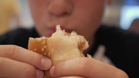 Ένα αγόρι σε έναν καφέ γρήγορου φαγητού Κατανάλωση των burgers και των τηγανιτών πατατών στους καφέδες γρήγορου φαγητού επιβλαβής φιλμ μικρού μήκους