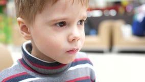 Ένα αγόρι σε έναν καφέ γρήγορου φαγητού που πίνει το ενωμένο με διοξείδιο του άνθρακα γλυκό ποτό μέσω ενός σωλήνα Στοματικός στεν απόθεμα βίντεο