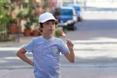Ένα αγόρι σε μια ριγωτή μπλούζα και μια ΚΑΠ Στοκ φωτογραφίες με δικαίωμα ελεύθερης χρήσης