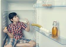 Ένα αγόρι σε ένα πουκάμισο και τα σορτς που τρώνε έναν croissant και πίνουν το γάλα μέσα σε ένα ψυγείο με τα τρόφιμα και το προϊό Στοκ Εικόνες