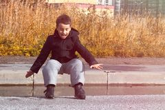 Ένα αγόρι σε ένα σκοτεινό σακάκι πηδά μια λακκούβα στο δρόμο στοκ φωτογραφία με δικαίωμα ελεύθερης χρήσης