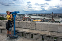 Ένα αγόρι στέκεται δίπλα σε ένα περισκόπιο που αγνοεί τον ποταμό Δούναβη στη Βουδαπέστη στην Ουγγαρία Στοκ φωτογραφία με δικαίωμα ελεύθερης χρήσης