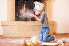 Ένα αγόρι στα καπέλα αρχιμαγείρων ` s κοντά στη συνεδρίαση εστιών στο πάτωμα κουζινών που λερώνεται με το αλεύρι, παίζοντας με τα Στοκ εικόνα με δικαίωμα ελεύθερης χρήσης