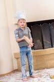 Ένα αγόρι στα καπέλα αρχιμαγείρων ` s κοντά στη συνεδρίαση εστιών στο πάτωμα κουζινών που λερώνεται με το αλεύρι, παίζοντας με τα Στοκ φωτογραφία με δικαίωμα ελεύθερης χρήσης