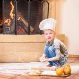 Ένα αγόρι στα καπέλα αρχιμαγείρων ` s κοντά στη συνεδρίαση εστιών στο πάτωμα κουζινών που λερώνεται με το αλεύρι, παίζοντας με τα Στοκ Εικόνα