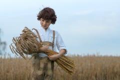 Ένα αγόρι στα παραδοσιακά βαυαρικά ενδύματα στέκεται στον τομέα Στοκ Εικόνες