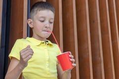 Ένα αγόρι στο κίτρινο πουκάμισο που στέκεται κοντά στον ξύλινο τοίχο, που κρατά ένα κόκκινο diaposable φλυτζάνι εγγράφου και που  στοκ εικόνες