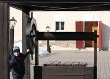 Ένα αγόρι συλλέγει το νερό από ένα φρεάτιο στοκ εικόνες