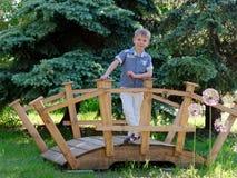 Ένα αγόρι 6 χρονών στέκεται σε μια όμορφη διακοσμητική γέφυρα στοκ φωτογραφία