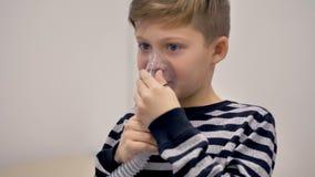 Ένα αγόρι outs σε μια inhaler μάσκα για μια ιατρική διαδικασία φιλμ μικρού μήκους