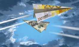 Ένα αεροπλάνο εγγράφου φιαγμένο από ευρο- σημείωση 200 πετά μετά από ένα άλλο αεροπλάνο φιαγμένο από ΗΠΑ η σημείωση 100 δολαρίων  στοκ εικόνα με δικαίωμα ελεύθερης χρήσης