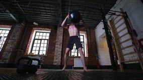 Ένα αθλητικό άτομο που παίρνει μια μεγάλη σφαίρα βάρους και που ρίχνει την απόθεμα βίντεο