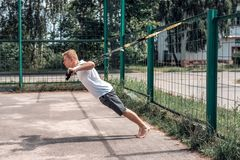 Ένα αθλητικό πρόσωπο, καθαρός αέρας συμμετέχει στην κατάρτιση trx, στα αθλητικά ενδύματα, το καλοκαίρι στην πόλη, που συστρέφει έ Στοκ Εικόνες