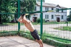 Ένα αθλητικό πρόσωπο, ο καθαρός αέρας συμμετέχει στην κατάρτιση trx, αθλητικά ενδύματα, το καλοκαίρι στην πόλη, που συστρέφει έξω Στοκ φωτογραφία με δικαίωμα ελεύθερης χρήσης