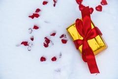Ένα αιφνιδιαστικό δώρο στο χρυσό φύλλο αλουμινίου και με ένα κόκκινο τόξο κορδελλών στο χιόνι την ημέρα του βαλεντίνου ενεργειακή στοκ εικόνες