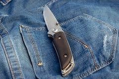 Ένα αιχμηρό μαχαίρι σε ένα υπόβαθρο τζιν στη φύση στοκ εικόνα με δικαίωμα ελεύθερης χρήσης