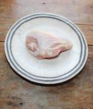 Ένα ακατέργαστο διασπασμένο στήθος κοτόπουλου σε ένα πιάτο σε έναν πίνακα στοκ εικόνες με δικαίωμα ελεύθερης χρήσης