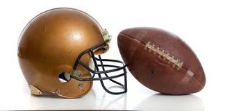 Ένα αναδρομικά χρυσά κράνος ποδοσφαίρου και ένα ποδόσφαιρο σε μια άσπρη ανασκόπηση Στοκ φωτογραφίες με δικαίωμα ελεύθερης χρήσης