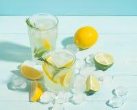 Ένα αναζωογονώντας ποτό ασβέστη λεμονιών με τους κύβους πάγου goblets γυαλιού σε ένα μπλε κλίμα Θερινό κοκτέιλ r στοκ εικόνα