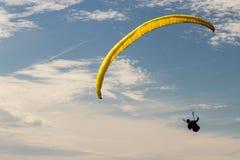 Ένα ανεμόπτερο επάνω στον ουρανό κατά τη διάρκεια μιας μύγας, που περιβάλλεται από το clou Στοκ εικόνα με δικαίωμα ελεύθερης χρήσης