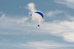 Ένα ανεμόπτερο επάνω στον ουρανό κατά τη διάρκεια μιας μύγας, που περιβάλλεται από το clou Στοκ Εικόνες